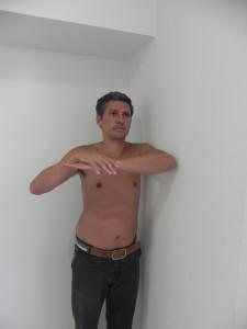 De pe encostado de lado na parede e com cotovelo na altura do ombro, empurra-se o punho para baixo