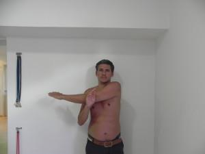 lado operado com cotovelo extendido na altura do ombro e o outro membro empurra o cotovelo junto ao corpo