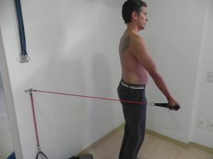 Com cotovelo extendido puxa-se o elastrico para frente, estando de costas para parede aonde o elástico esta preso